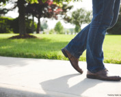 Legs in blue jeans and brown shoes walking next to grassy area